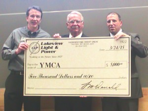 Members of Lakeview Light & Power holding a donation check to the local YMCA